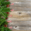 Christmas border with evergreen branches and candy canes on rust — Stock Photo #78314862
