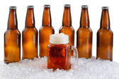 Glass of beer with six pack of ice cold bottles isolated on whit — Stock Photo