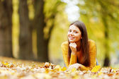 Cute woman laying in autumn park — Foto Stock