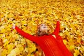 Woman laying on autumn leaves — Stock Photo