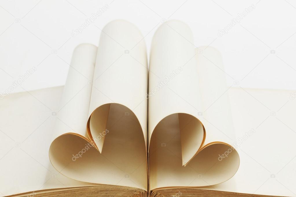 翻开的书页卷在心形状上白色孤立