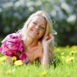 Woman laying on flower meadow — Stock Photo #69649949