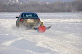 The car carrying the man on ice-boat  in tow in the snow — Stock fotografie