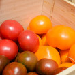Red and yellow tomatoes in wooden crates — Stock Photo #77620692