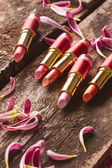 Lipsticks with flower petals — Stock Photo