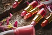 Lipsticks with nail polish and flower petals — Stock Photo