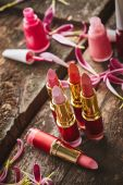 Lipsticks, nail polish and flower petals — Stock Photo