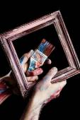 Paintbrush and vintage frame in hands — Stock Photo