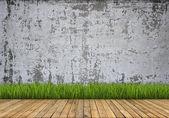 Arrière-plan. Mur en béton et plancher en bois avec de l'herbe — Photo