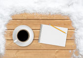 Coffee, pencil and notebook on the planks covered with snow — Stock Photo
