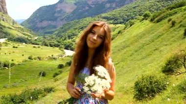 Happy young girl with a bouquet of daisies in a meadow in the mountains — Stock Video