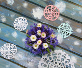 Lovely paper snowflakes and a bouquet of flowers on a blue woode — Stock Photo