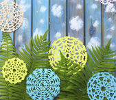 Carved green fern leaves and paper snowflakes on a blue wooden b — Stock Photo