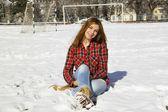 Gelukkig jong meisje, zittend op de sneeuw in het park op een zonnige wint — Stockfoto