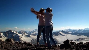 Two happy girls hugging in the top of the mountain with his arms raised above his head in celebration of reaching the top of the mountain — Stock Video