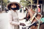 Vietnamese woman wearing a Conical Asian hat standing by a horse — Stock Photo
