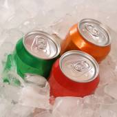 Cola and lemonade beverages in cans on ice — Stock Photo