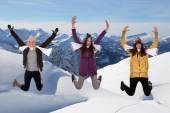 Happy young women jumping in winter in the mountains — Stockfoto