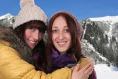 Two smiling women hug each other in the mountains — Stockfoto