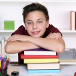 Young student holding his head on a stack of books at school — Stock Photo #54931307