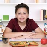 Happy smiling boy doing homework at school — Stock fotografie #54931423