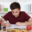 Young student writing in his exercise book at school — Stock Photo #54932309