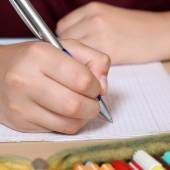 Student writing with hand in his exercise book at school — Stock Photo