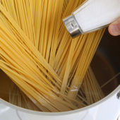 Cooking spaghetti noodles pasta meal salting water in the pot — Stock Photo