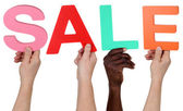 Multi ethnic group of people holding the word Sale — Stock Photo