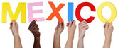 Multi ethnic group of people holding the word Mexico — Stock Photo
