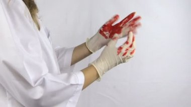 Woman surgeon doctor in white robe take off bloody gloves hands — 图库视频影像