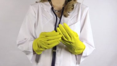 Hand uncover large yellow rubber glove and pick neck stethoscope — Stock Video