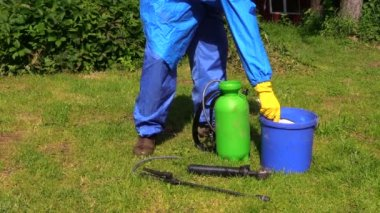 Man with chemistryproof clothing hand pour fertilizer to spray — Stock Video