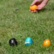 Traditional Easter game. Hand throw roll colorful eggs on grass. — Stock Video #52395407