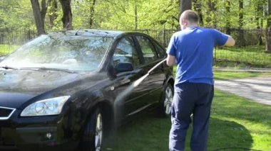 Worker wash black car outdoor with high pressure water equipment — Stock Video