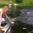 Girl run paper boat over fast flowing stream green park summer — Video Stock #52487815