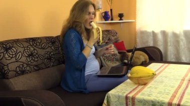 Happy pregnant woman caress her belly eat grape and watch TV — Stock Video