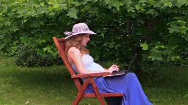 Pregnant woman with hat work with laptop sitting on wooden chair — Stock Video