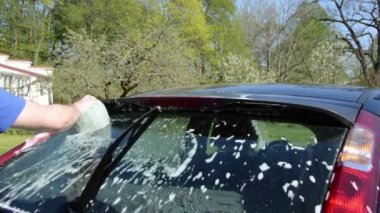 Closeup of man with soapy sponge clean wash back car glass — Stock Video