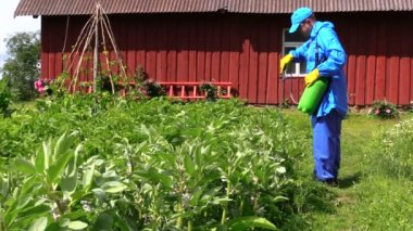Man in blue clothes mix fertilizer in sprayer at potato field — Stock video