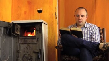 Man read book sip wine next to ancient smoldering fire stove — Stock Video