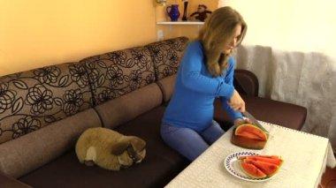 Schwangere frau schneidet wassermelone und in tabelle im wohnzimmer. — Stockvideo