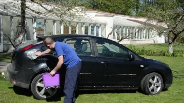 Man with bucket of soap water and sponge clean favourite car — Stock Video