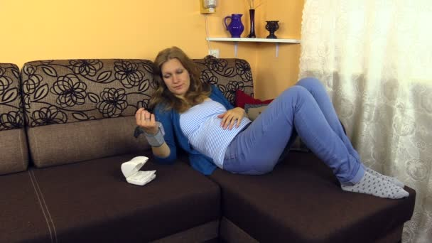 Tired pregnant woman lie on couch measure her blood pressure