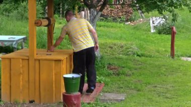 Farmer man at well house draw water and pour into bucket — Stock Video