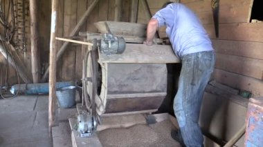 Farmer man spin handle of sifting machine and sift grain in mill — Stock Video