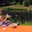 Girl make paper boat sit on plaid near ripply stream on summer — Video Stock #53281221