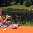 Girl make paper boat sit on plaid near ripply stream on summer — 图库视频影像 #53281221