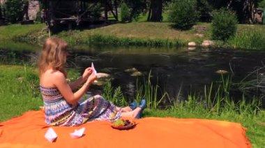Girl make paper boat sit on plaid near ripply stream on summer — Stock Video