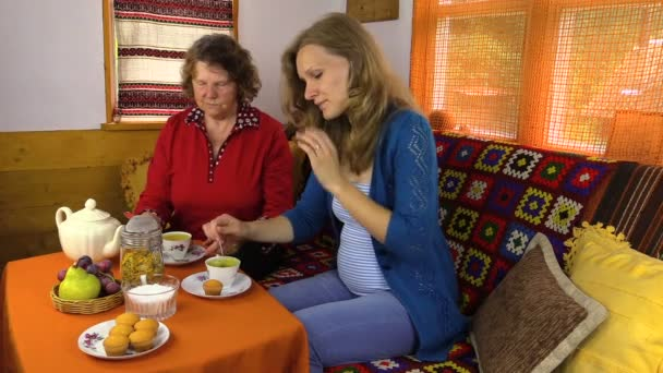 Senior old woman with pregnant daughter drink marigold tea